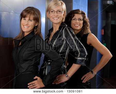 Team portrait of happy young businesswomen smiling in corporate office lobby.