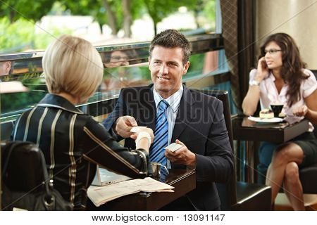 Young businessman and businesswoman having a meeting in cafe, exchanging business cards.