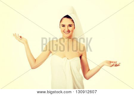Spa woman wrapped in towel showing copyspace in hands