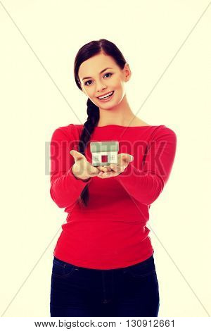 Smiling young woman holding house model