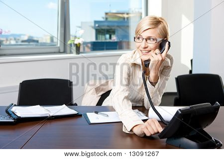 Young businesswoman sitting at desk in office, talking on landline phone, smiling.