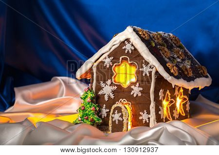 Christmas glazed gingerbread house with sweet pine and walnuts on housetop. Against blue silk background.