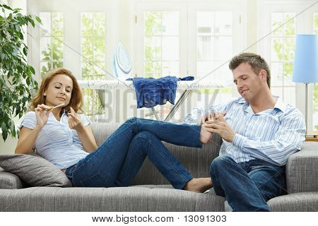 Couple relaxing at home on sofa, man giving foot massage to her gildfriend.
