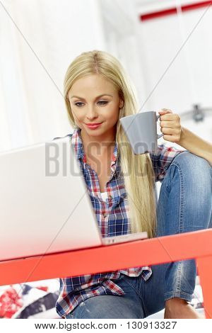 Young woman sitting at desk at home, using laptop, drinking tea.