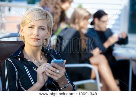 Joven empresaria mediante teléfono móvil elegante, fuera del edificio de oficinas.