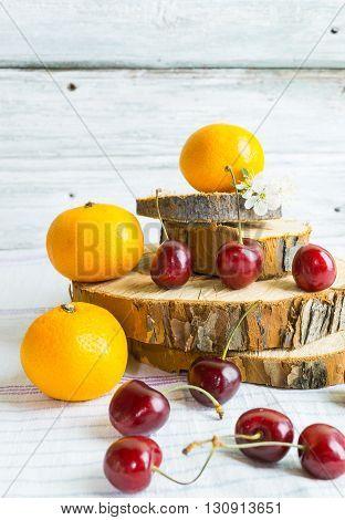Red cherries heap merry and orange mandarin on wooden rustic plate