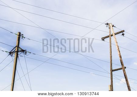 Old power poles against a blue sky
