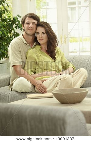 Young couple sitting together on couch at home, embracing, smiling.