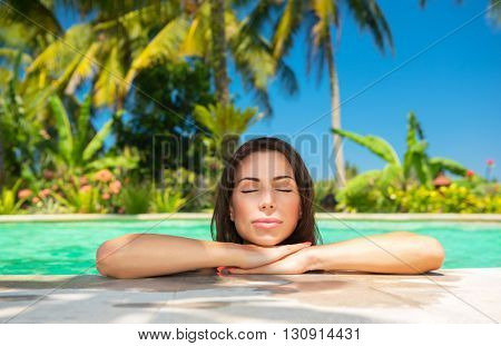 Closeup portrait of a beautiful calm female with closed eyes enjoying bright warm sun light, relaxation in a swimming pool, luxury summer vacation