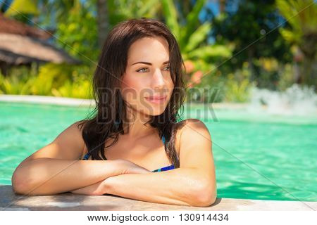 Portrait of a nice female on a tropical beach resort, relaxing in a swimming pool, enjoying summer vacation on a spa resort