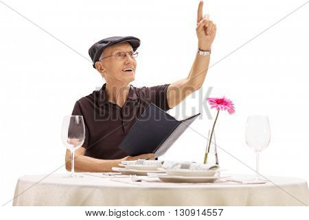 Senior gentleman holding a menu and calling a waiter in a restaurant isolated on white background