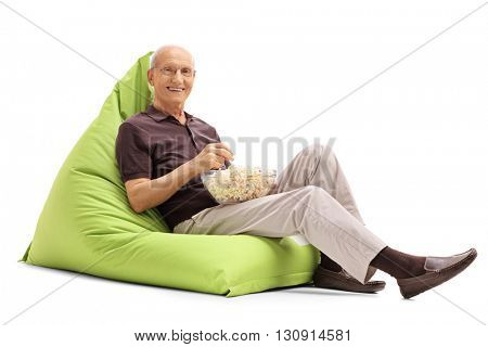 Senior man eating popcorn seated on a green beanbag and looking at the camera isolated on white background