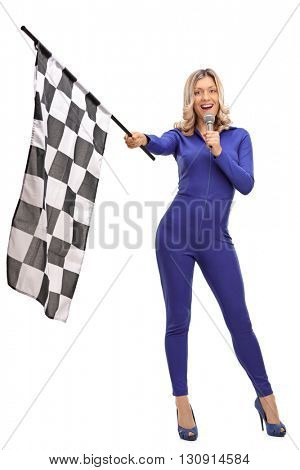 Full length portrait of a racing woman waving a race flag and speaking on a microphone isolated on white background