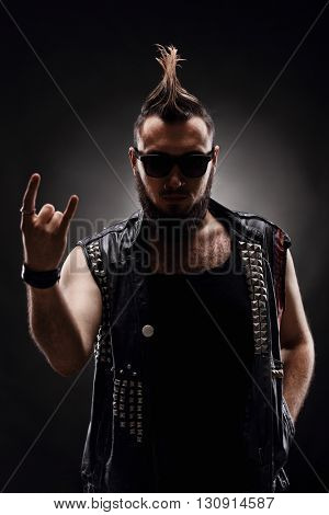 Vertical shot of a punk rocker making a hardcore hand gesture on dark background