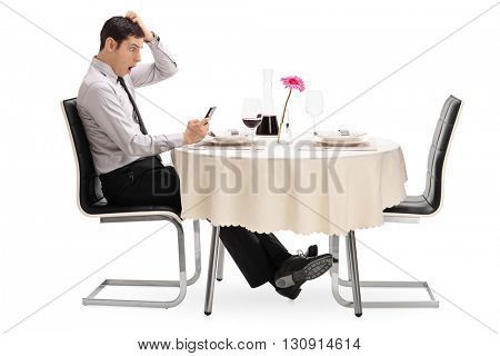 Surprised young man looking at his cell phone seated at a restaurant table isolated on white background