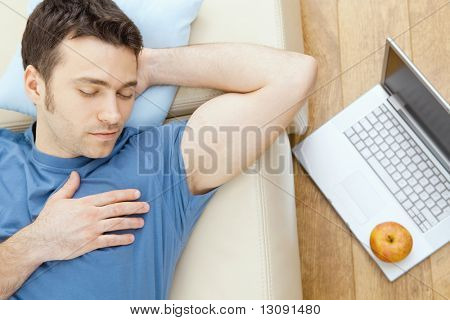 Young man sleeping on sofa at home, laptop on floor.  Overhead view.