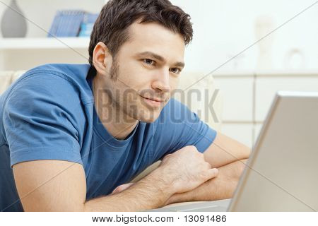 Happy young man laying on sofa and using laptop computer at home, smiling.