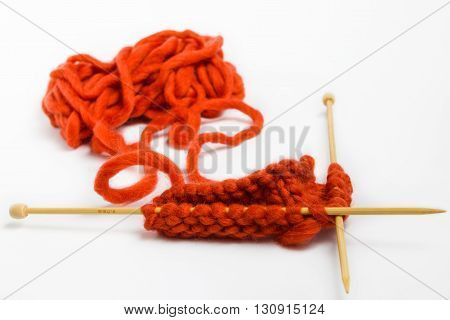 Knitting with wool thick soft orange color yarn on the needles. Yarn and knitting needles isolated on white background.