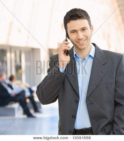 Portrait of happy businessman talking on mobile in office hallway.