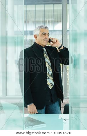 Nature businessman standing behind desk in modern glass office, talking on mobile phone.