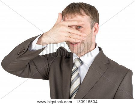Surprised young man hiding eyes behind his hand isolated on white background