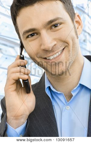 Closeup portrait of happy businessman talking on mobile in front of office building windows.