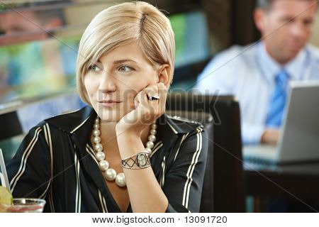 Closeup portrait of young woman sitting at table in cafe, thinking leaning on her hand.
