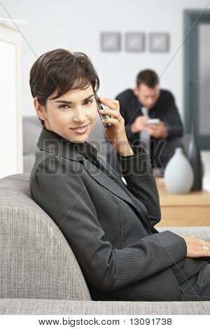 Happy young businesswoman sitting on sofa at office talking on mobile phone, smiling.