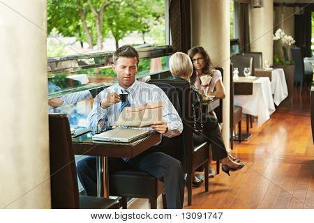 Businessman sitting at table in cafe, reading newspaper and drinking coffee. Young women talking in the background.