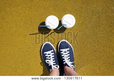 Female Feet In Blue Sneakers And Two Cups Of Coffee On A Sunny Day