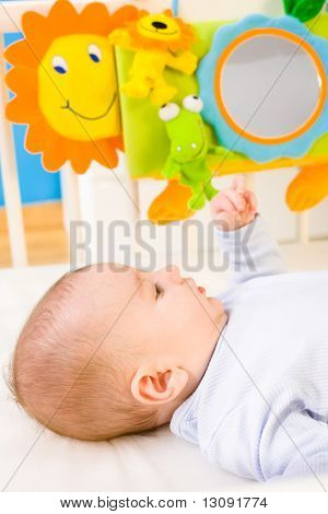 Infant baby lying in baby bed at children's room. Toys are officially property released.