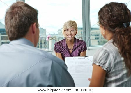 Happy woman applicant talking during job interview. Over the shoulder view.