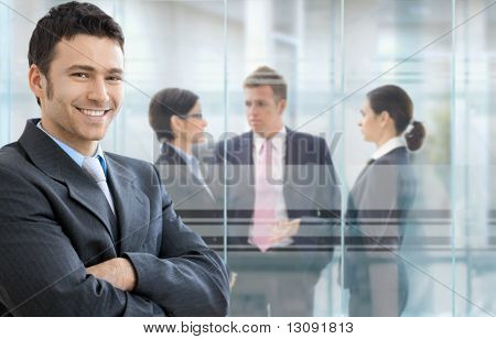 Businessman standing in downtown office, businesspeople talking in background in front of windows.