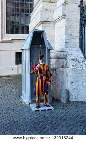 VATICAN CITY - MAY 5 2014: unidentified Papal Swiss guard standing at the Vatican Museums door in the Vatican. The Swiss guards served since the late 15th century.