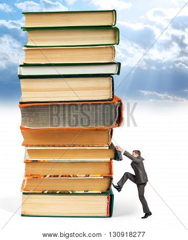 Pile of books with businessman climbing it on blue sky background