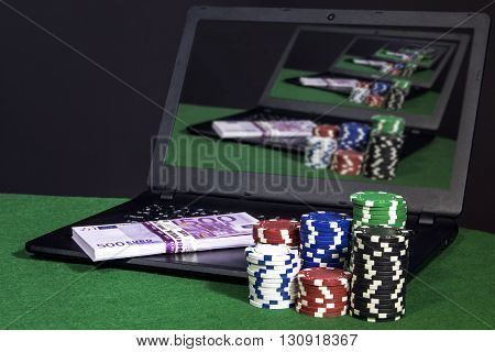 Laptop with money and poker chips on the table