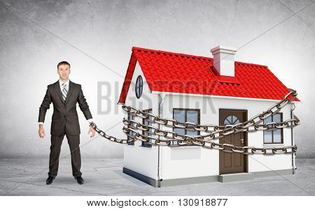 Businessman chained to house on grey background