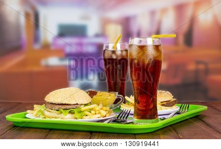 Two servings of hamburgers, french fries, cola and sauce on background halls cafes.