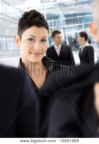 Young businesswoman standing among other businesspeople otside of office building.