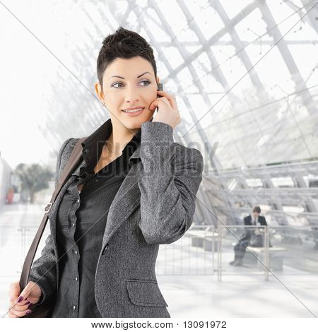 Portrait of young businesswoman talking on mobile phone on office lounge.