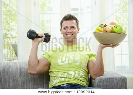 Muscular man sitting on sofa, holding barbell and bowl of fruits in hand, smiling.