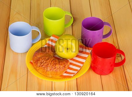 Bright cups and disposable plate with a croissant and an apple on a background of light wood.