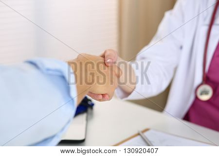 Female medicine doctor shake hand as hello with male patient in office closeup. Welcoming friend introduction or thanks gesture. Tests advertisement concept. Physician ready to examine patient
