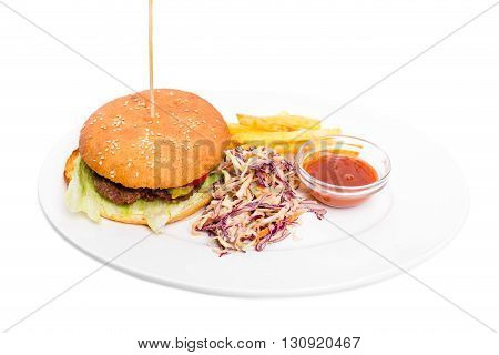 Delicious lamb burger with french fries and coleslaw salad. Served with delicious ketchup. Isolated on a white background.