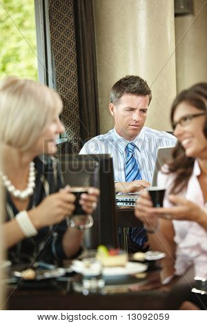 Businessman using laptop in cafe, young woman drinking coffee and talking in the foreground. Selective focus on businessman.