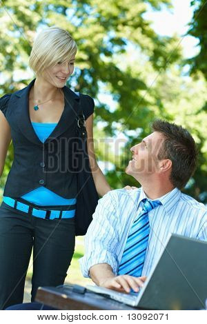 Casual businessman using laptopn in park summertime, while waitinf for young woman, who just arrived.