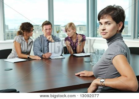 Panel of business people sitting at table in meeting room conducting job interview. Applicant looking at camera.