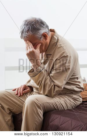 Worried senior man can not sleep. He is sitting on his bed with headache.