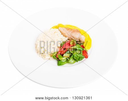 Roasted chicken fillet with rice and fresh vegetables as a garnish. Served with delicious saffron mousse. Isolated on a white background.