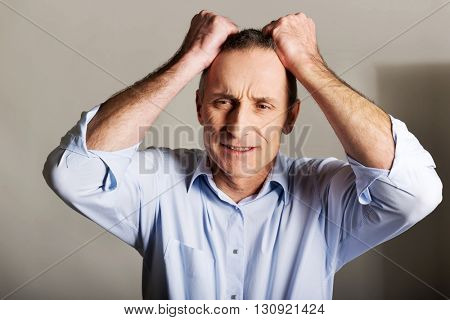 Portrait of frustrated man pulling his hair